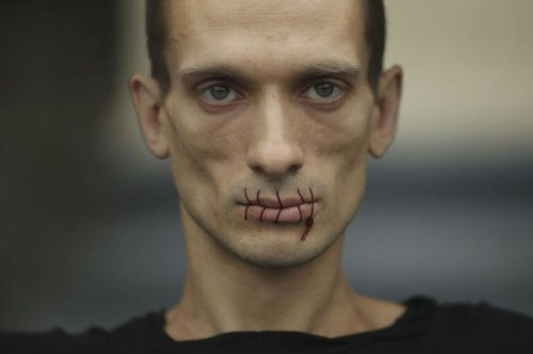 """Artist Pyotr Pavlensky, a supporter of jailed members of female punk band """"Pussy Riot"""", looks on with his mouth sewed up as he protests outside the Kazan Cathedral in St. Petersburg, July 23, 2012. A court on Monday rejected a request to call President Vladimir Putin and the head of the Russian Orthodox Church to testify in the trial of three female punk rockers who derided Putin in a protest in the country's main cathedral, their lawyer said. Picture taken July 23, 2012.  REUTERS/Trend Photo Agency/Handout  (RUSSIA - Tags: CIVIL UNREST CRIME LAW SOCIETY RELIGION POLITICS TPX IMAGES OF THE DAY)"""